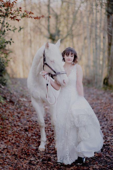 une mariée dans les bois avec son cheval blanc pres de lyon